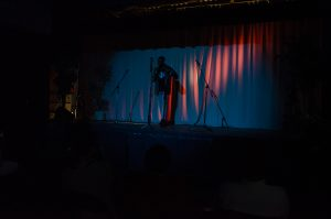 A dark photo showing a person standing up on stage in front of a microphone.