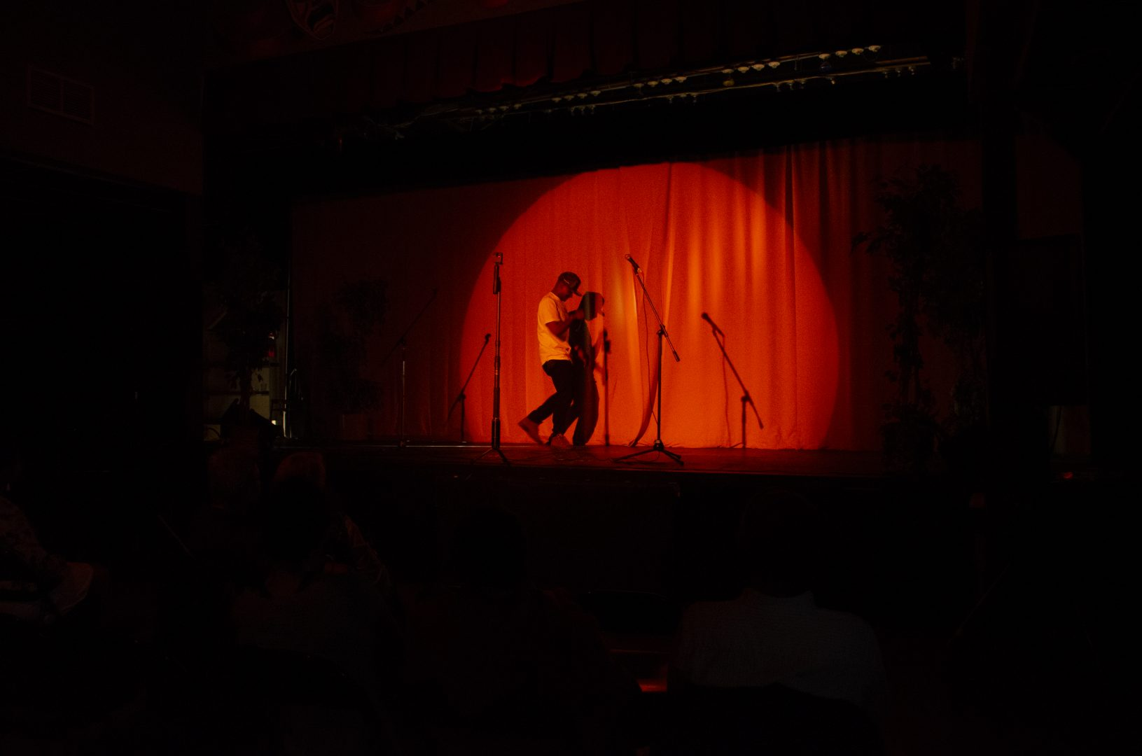 Steve Harmony performing on stage, in motion, with a bright light in the shape of a circle, revealing the red curtain behind. There is darkness surrounding everywhere else.