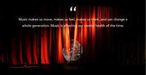 """A photo of a red curtain on a stage with a light shining in the middle through the darkness with a quote overlaid on top in white """"Music makes us move, makes us feel, makes us think, and can change a whole generation. Music is affecting our mental health all the time."""""""