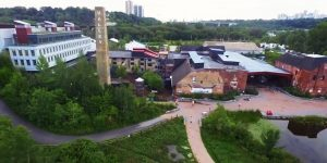 An aerial shot of the Toronto Brickworks building, taken in the summer with lush greenery surrounding the building. You can see a bit of the city skyline off in the distance.