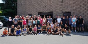 A group photo of dozens of people all dressed in workout clothes. The photo was taken outside in a parking lot, with a brick building behind them.