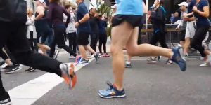 A crowd of people running, taken low to the ground, only showing people from the waist up. In the foreground is a person with shorts on and one foot up, mid-stride.