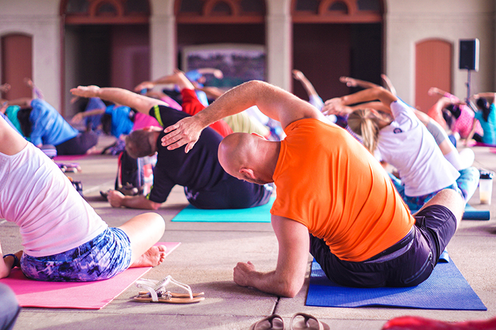 A photo of a crowd of people in a yoga class, sitting down on yoga mats with their right arms up over their heads, leaning to the left. In the foreground is a person wearing a bright orange shirt, sitting on a blue mat.