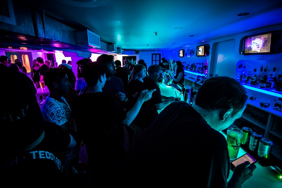 A wide angle view of Power Up Bar at the Linkin Park tribute party. A large group of people in bright purple and blue neon light.