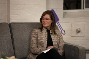 Martha McGroarty sitting on a couch, wearing a checkered blazer and clear rimmed glasses.