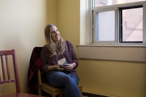Stephanie Mather sitting down, smiling and looking off to the right