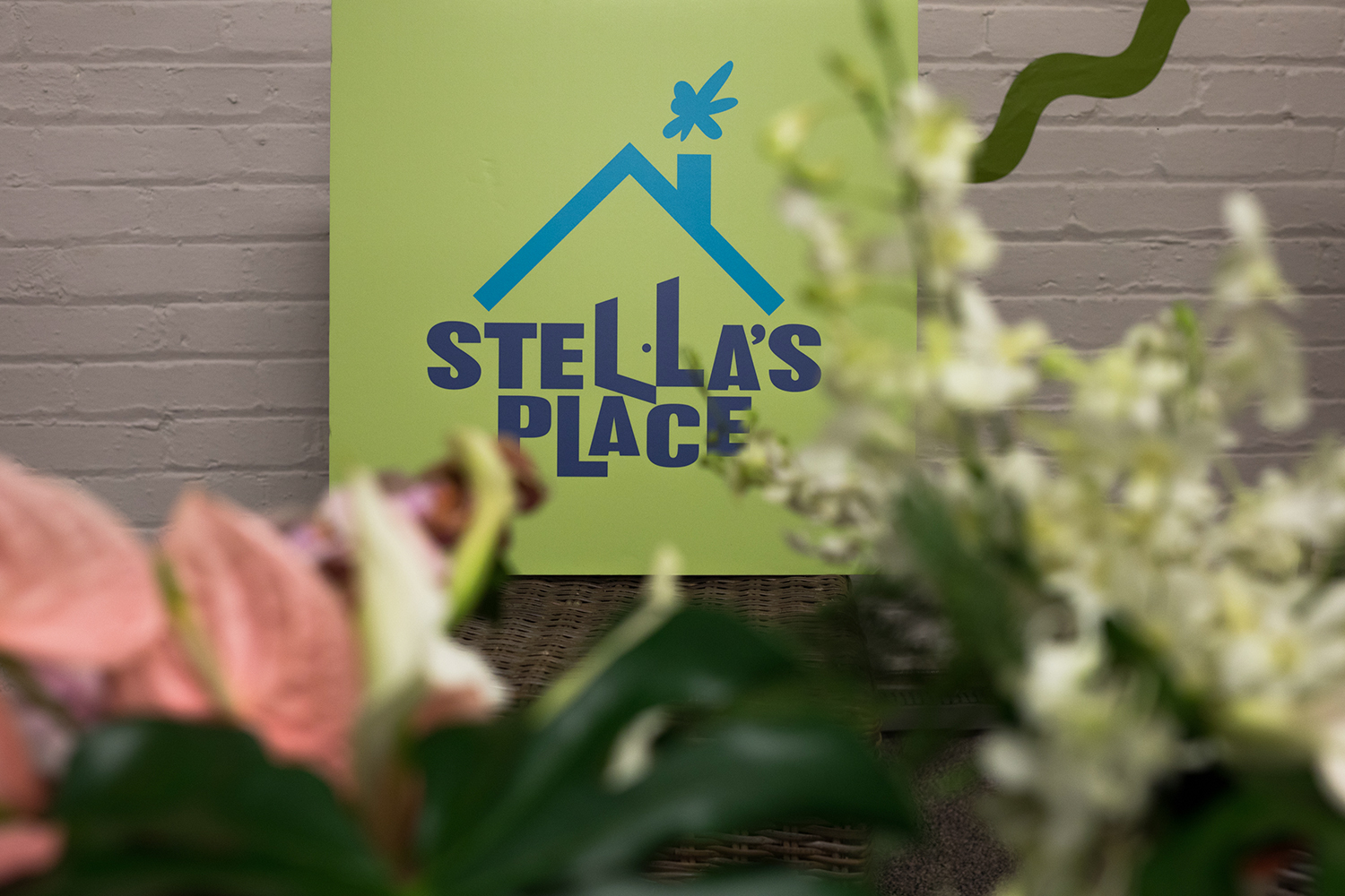 A printed canvas of the Stella's Place purple and blue logo on a lime green board. Blurred in the foreground are pink, white and green flowers.
