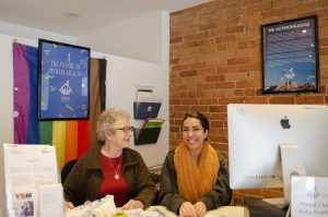 Stella's Place volunteer Liz, pictured with Access Team Member, Nakeesa behind Stella's Place front desk in the café.