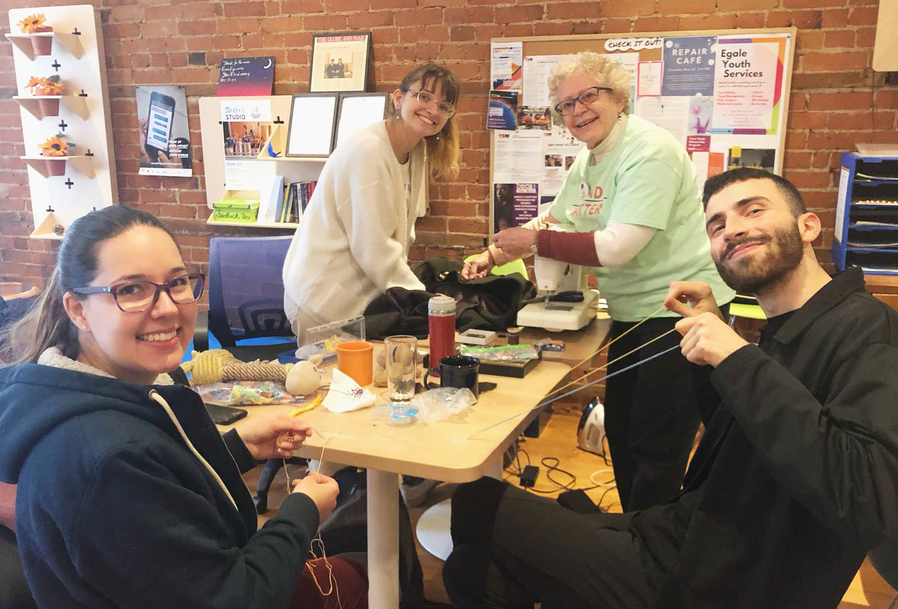 4 people in Stella's Place café gathered at a table andposing for a photo