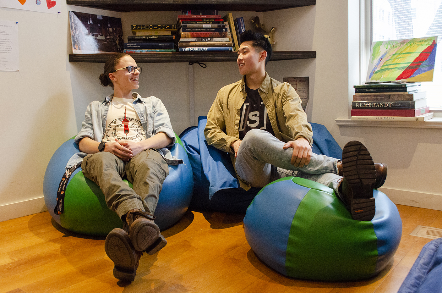 Wing and Alex laughing and looking at each other sitting on bean bags in the Stella's Place cafe