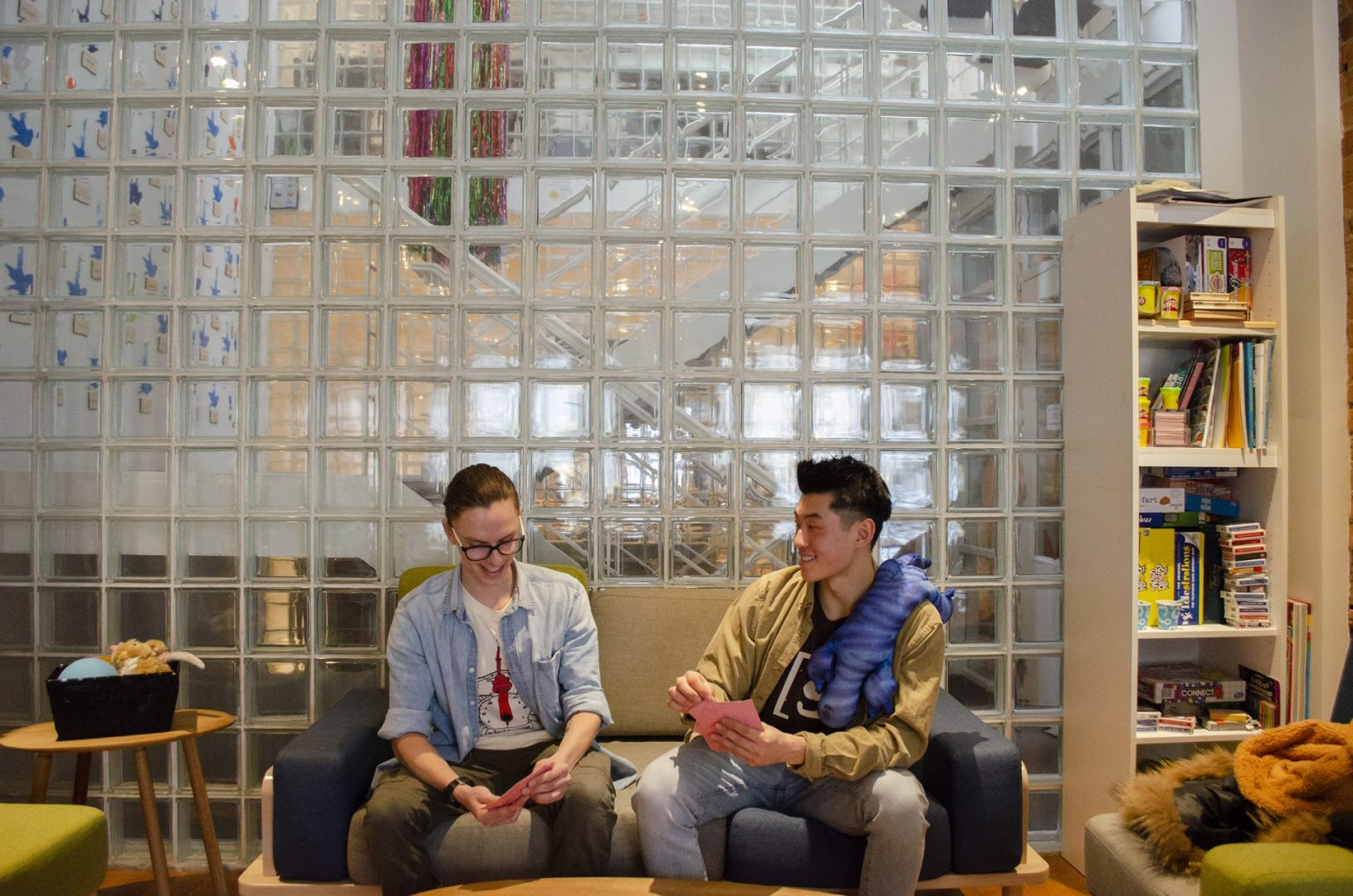 Alex and Wing sitting together on the couch in the Stella's Place cafe with a big tiled glass wall in the background