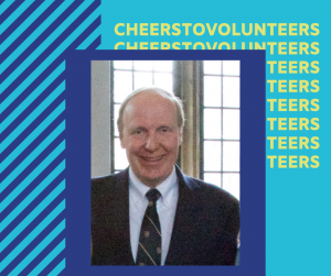 """A portrait of Geoff wearing a black suit and tie. The image has a purple border around and is in the middle of a blue graphic with text repeated and obstructed behind the photo that reads """"Cheers to volunteers"""""""