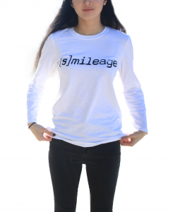 """Photo of person with long hair from the neck down wearingwhite longsleeve t-shirt that says '[Smile]age"""" across the chest"""