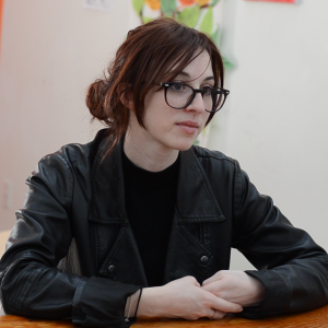 A portrait of Samantha Ledamun, sitting down with her arms folded in front of her, looking off to the right. Sam is wearing a black leather jacket, has black rimmed glasses and dark red hair.