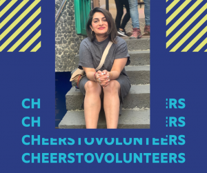 Portrait of Sara sitting down on stairs, smiling at the camera on background with purple and green graphics and text that reads 'Cheers to Volunteers'