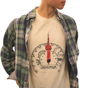 Photo of person from the neck down wearing white t-shirt with graphic of speedometer illustrated with Toronto buildings around and a red CN tower. Reads [Smile]age in black below