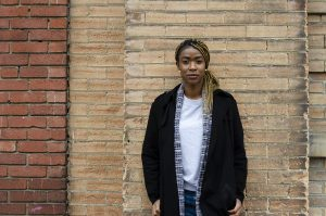 Portrait of Lereen with long hair hanging over one shoulder, wearing a white shirt with a black coat overtop. She is standing against a brown brick wall with her hands in her pockets. Lereen is staring straight into the camera with a serious, determined expression.