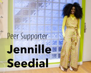 """A portrait of Jennille standing to the right of the photo, wearing a bright lime green outfit. On the left side of the image in large letters """"Peer Supporter"""" and bolded """"Jennille Seedial"""""""