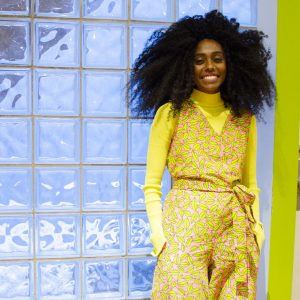 A portrait of Jennille standing to the right of the photo, wearing a bright lime green outfit and standing in front of a wall of square tiled windows.