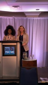 A photo of Peer Supporter, Jennille and Clinician, Miriam, standing, smiling behind a podium. On the podium it says 'FRAYME' and behind them is a curtain which appears purple from the lighting in the room.