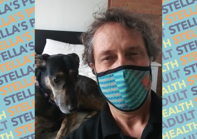 Photo of person wearing Stella's Place mask, posing with a dog, blue patterned background