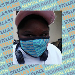 Photo of person wearing Stella's Place mask, blue patterned background