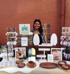 Image of person standing behind display of jewlery with brick background.