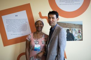 Carol Clarke (left) standing next to John Choi (right), posing for the camera in front of a wall with orange graphic stickers and posters