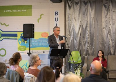 Dr. Bjug speaking at a podium in front of a crowd of people at the World Mental Health Day panel event, 2019