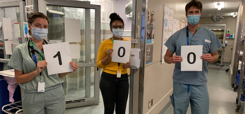 Pathway to Peers program celebrates its 100th patient. A photo of 3 people holding up number signs for '100' taken in a hospital room