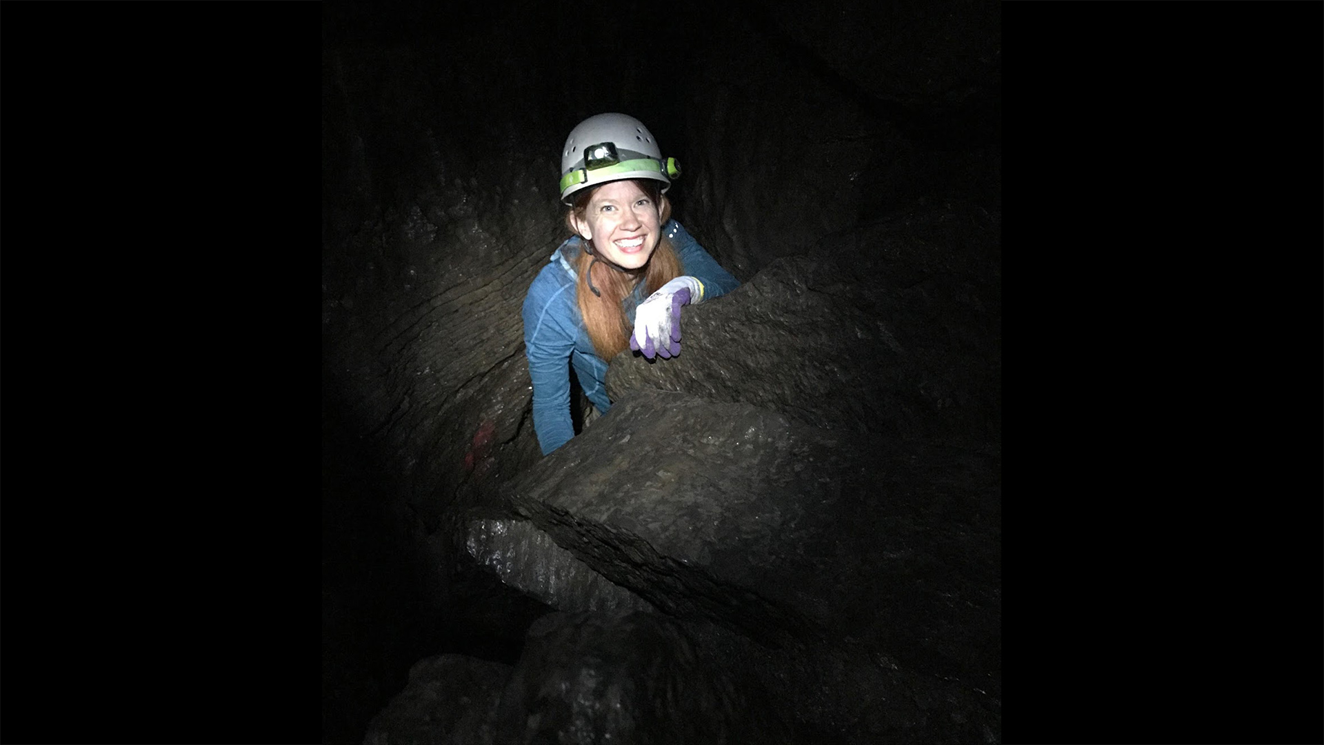 Photograph of Carol Krause in a dark cave. She is fair skinned with long orange hair, in this photo she is wearing a light blue sweater and has a big smile on her face, showing all of her teeth. On her head is a safety helmet with a light attached that is the only source of light in the photo. She has white gloves on her hand and is holding onto the rock in front of her. Only the top half (above her torso) is showing and the rest is behind more rocks.
