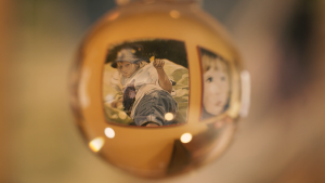 A photo with a warm yellow hue looking through a glass ball to a painting of a child, which makes the painting look distorted through the glass.