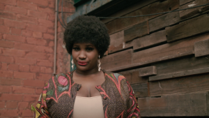 Photo of Sydellia Ndiaye, standing in front of a red brick wall. Sydellia is wearing a colourful cardigan with pink blue and yellow graphics, overtop of a white shirt underneath. She has long white dangle earrings that almost reach her shoulders. She's wearing red lipstick and has a small smile on her face.