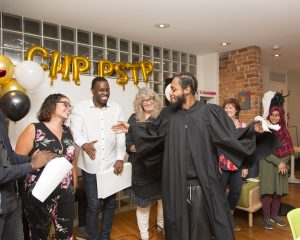 A photo of a person graduating from the Community Healing Project. They have their hand outstretched, about to shake someone's hand and is wearing a black graduation robe. Everyone around them is smiling and looking at them.