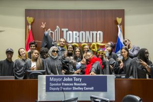 """A group photo of the Community Healing Project team, all making funny faces for the camera, and dressed in black graduation gowns and some wearing feather boas and sunglasses. they are standing in front of a city of Toronto sign and behind a podium that says """"Mayor John Tory"""""""