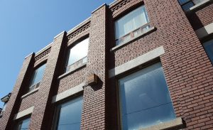 A photo taken from the outside of the new Stella's Place building. It's taken from right outside the building looking up, giving it a feeling of growth. The brick is red and the sky is bright blue which is reflected onto the windows.