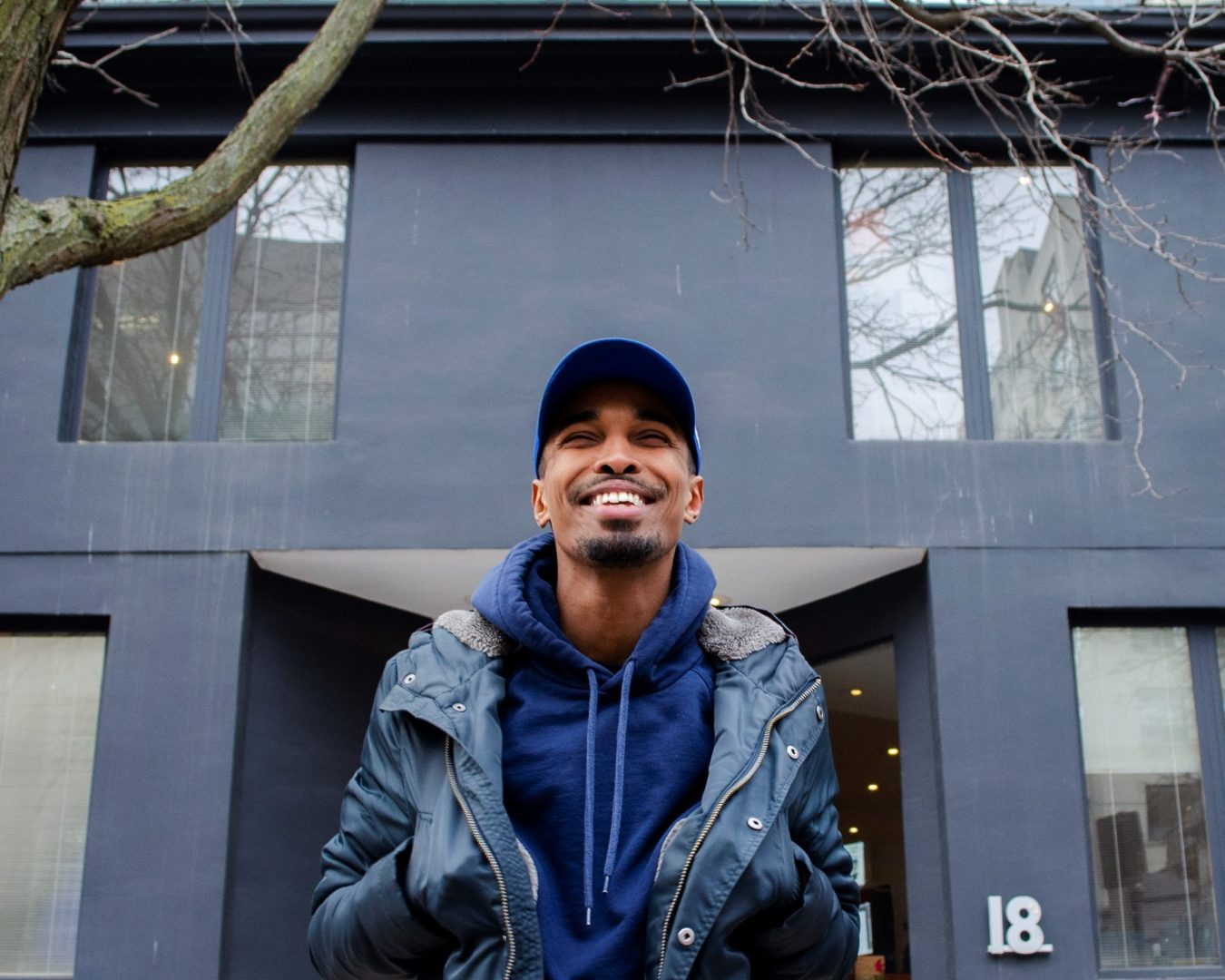 A portrait of Abdul standing outside of the Stella's Place building, smiling, with hands inside their blue jacket. They are wearing a blue baseball cap and a blue hoodie underneath the coat.