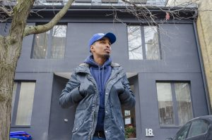 A poirtrait of Abdul standing outside of the Stella's Place building, looking off into the distance with hands inside their blue jacket. They are wearing a blue baseball cap and a blue hoodie underneath the coat.