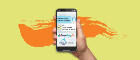 A light green graphic with an illustration in the middle of a hand holding a phone with the BeanBagChat app on the screen. Behind the phone in the background is an orange graphic paint swipe element.