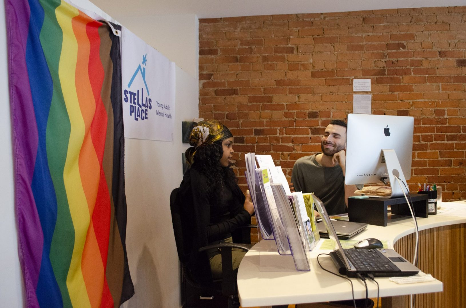 Two Stella's Place Access Coordinators sitting behind the front desk in Stella's Place front cafe space. The Access Coordinators are sitting down speaking to each other. Behind them is a large rainbow Pride Flag, a poster with Stella's Place logo and a red brick wall.