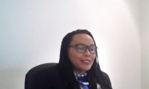 A screenshot of Wangari speaking at the Review & Reimagine Panel Event