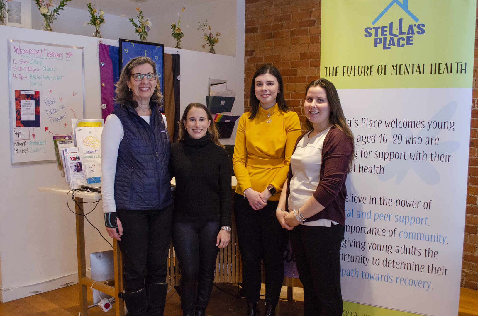 A group photo of the Aubrey & Marla Dan Foundation standing with Founder, Donna Green, and Peer Initiatives Manager, Allison Dunning in the Stella's Place café.