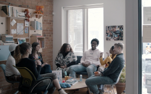 A photo of a bunch of people in the Stella's Place café, sitting down in a circle, all laughing together