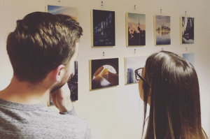A photo of the back of 2 people who are looking at photos hung up on a gallery wall.