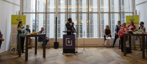 A photo from a donor recognition event. A person is speaking in the middle of the room into a microphone, with a group on both sides looking at them. The room is very open with lots of light coming in from the floor to ceiling windows behind.