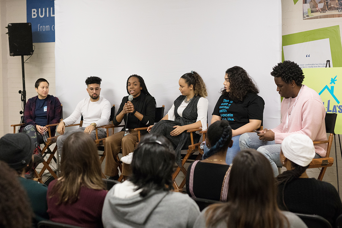 A group of people sit on a panel following a film screening at Stella's Place. In the foreground slightly blurred out is the audience and behind the panelists is the white, blank projector screen.
