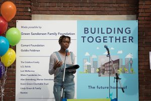 """Lereen speaks at the Building Together event, standing in front of a microphone. Behind Lereen is a large banner that reads """"Building Together"""" and to the left, a bouquet of brightly coloured balloons."""