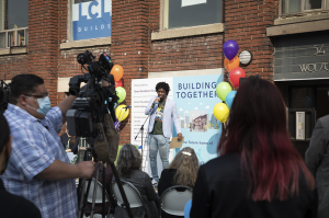 Image of Asante outside the new building at the launch event. Asante is speaking into a microphone on a stage with an audience in the foreground, and a camera crew. You can see the label '54 Wolseley' on the red brick building and some of the windows. Behind Asante is a big graphic board that says 'Building Together' framed by colourful balloons.