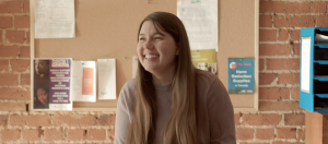 A photo of Mara in the Stella's Place café. The photo is from the waist up and they are laughing, looking to the left. Mara is wearing a muted brown turtleneck and has long brunette hair.