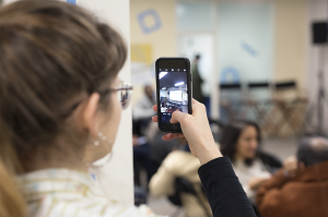 A photo of a person taking a photo on an iPhone. The depth of field is very shallow and only the hand and phone are in focus. You can see the person's head in the foreground and a crowd in the background blurred out of focus.